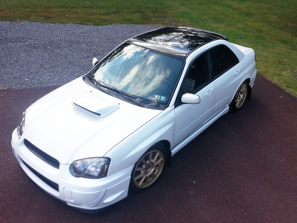 Gloss black vinyl roof wrap on a Subaru WRX STI